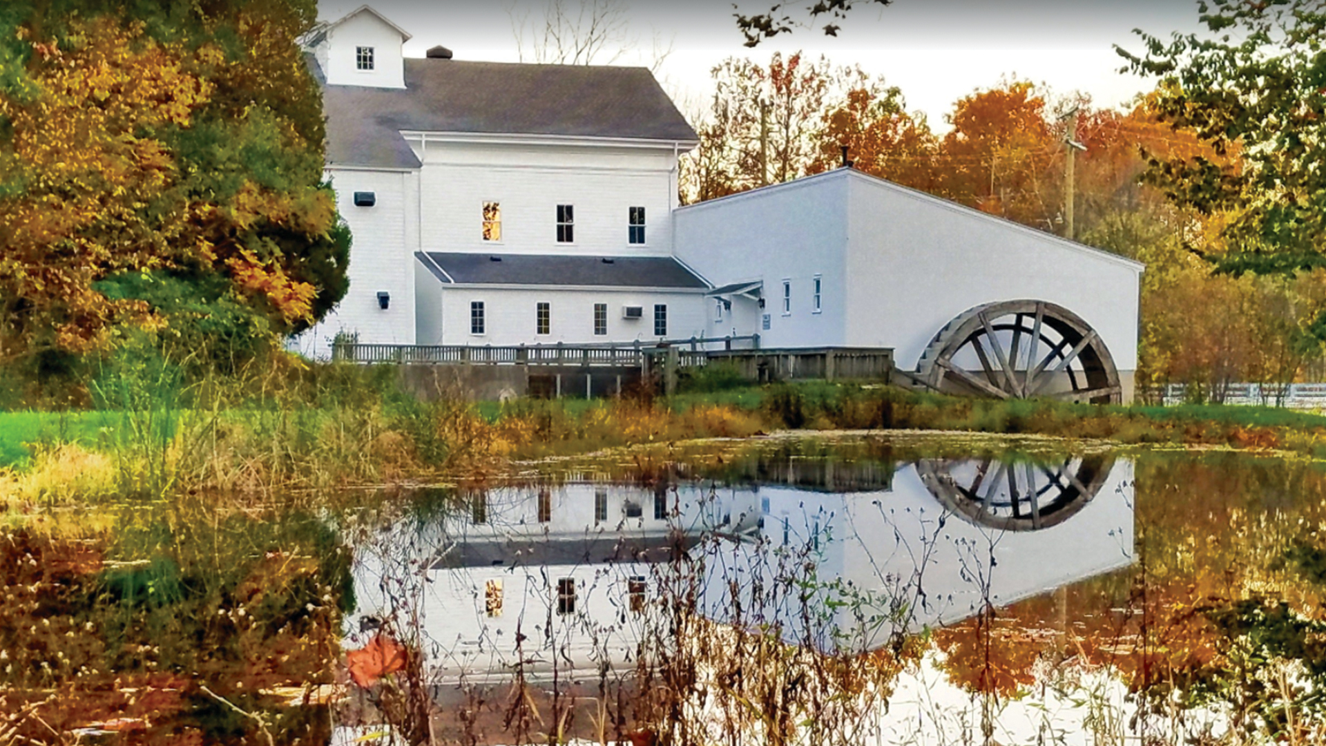 Beautiful side view of the Wolcott Mill Metropark Farm House in Fall